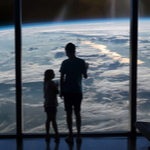 parent and kid looking at the earth from space station